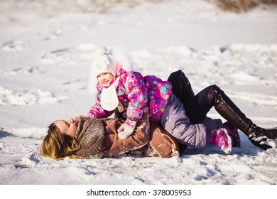 Mom and daughter playing in the snow a sunny winter day