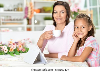 Mom and daughter are playing a tablet