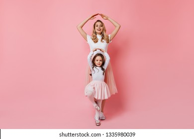 Mom and daughter pose as ballerinas on pink background. Portrait of curly adult blonde woman in white T-shirt and her younger sister in tutu