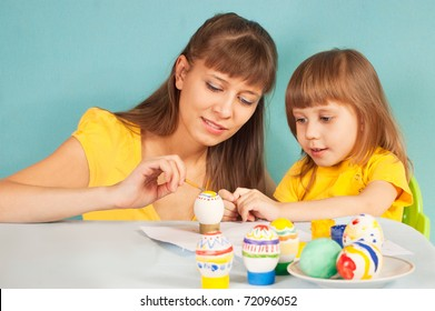 Mom and daughter are preparing for the Easter painted eggs