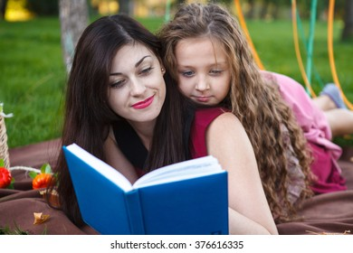 Mom and daughter reading a book lying on the plaid in the park