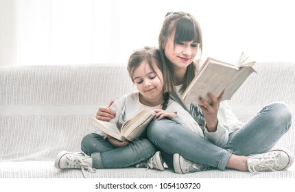 Mom and daughter reading a book on the couch, the concept of family comfort and family relations