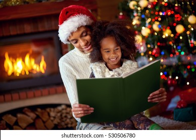 mom and daughter reading Christmas fairytales in near Christmas tree indoor