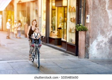 Mom with daughter riding bike in Italy. Child sitting in safety seat. Old narrow italian town. Sport healthy family activity. Summer european vacation. Happy travelling concept