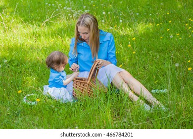 Mom and daughter in the same dress in the forest with a basket