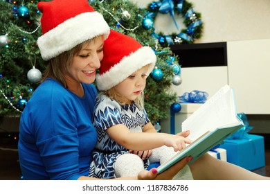 Mom and daughter in santa hat reading fairy tales near the Christmas tree