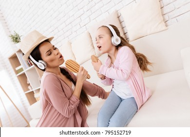 Mom and daughter sing songs at home. They use combs like microphones. They play together.