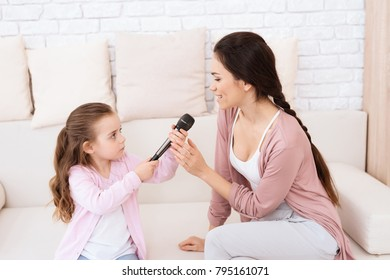 Mom and daughter sing songs at home. They use microphones for karaoke. They play together.