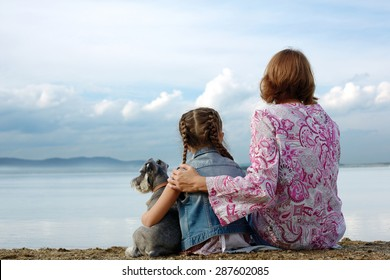 Mom and daughter sit embracing on the lake and look at the water. Near them sits their small dog.