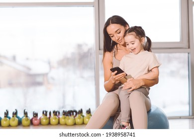 Mom and daughter sit in a gymnastic ball and look telephone