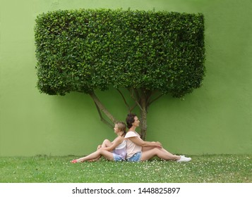 mom and daughter are sitting back to back under a green tree