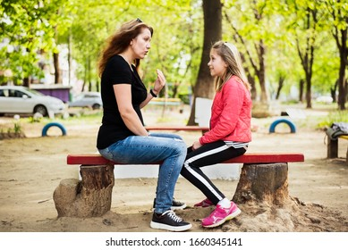 Mom and daughter sitting on a bench and talking, woman trying to impart to teenage daughter a woman's wisdom, intuition. The daughter smiles and doesn't understand what mom wants to tell her
