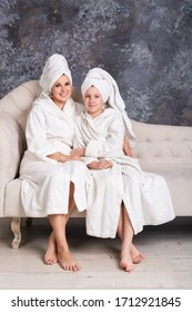 Mom and daughter are sitting on the couch in bathrobes. Spa. Home care.
