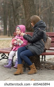 Mom and daughter are sitting on a park bench.