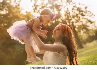 Mom and daughter sitting in the park on the grass