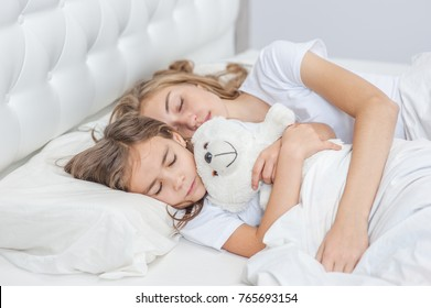 Mom and daughter sleep together on the bed in the bedroom