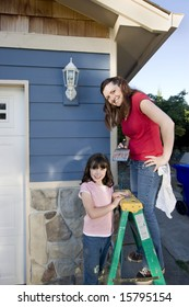 Mom and daughter smiling as they paint the house. Vertically framed photograph