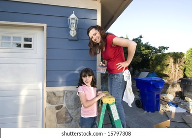 Mom and daughter smiling as they paint the house.. Horizontally framed photograph