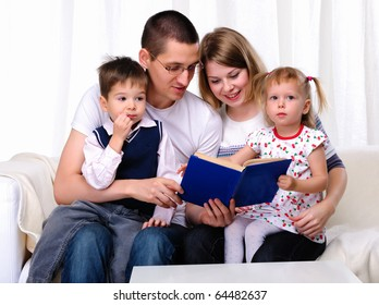 Mom, daughter, son and dad reading a book together on the couch