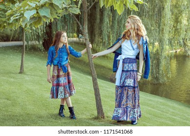 Mom and daughter are standing by the lake. They are dressed in the style of a boho.