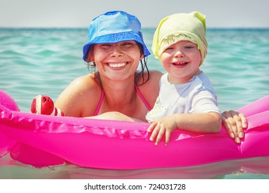 Mom and daughter are swimming in blue sea water on inflatable mattress. Happy smiling family on vacation. Woman and child bathing on bright sunny day at sea