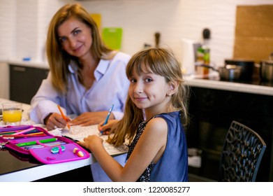 Mom and daughter at the table draw. mother learns with the child at home.