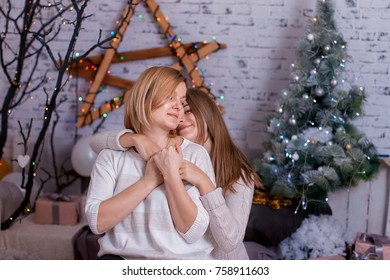 Mom and daughter with a teenager, gently embrace, against the backdrop of the New Year's decor