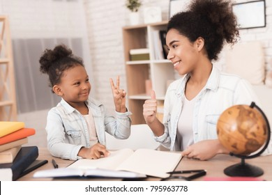 Mom and daughter together do their homework in school. They are both African American. Mom helps a little girl learn.