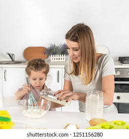 Mom and daughter together make the dough for baking in the kitchen at home.  Mom pours milk from a bottle into a bowl of flour, the girl holds a whisk in her hand
