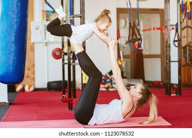 Mom and daughter together perform different exercises in the gym