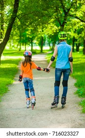 Mom and daughter together rollerblading. Back view