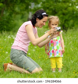 Mom and daughter together take pictures. Mom teaches young daughter photographing outdoors.