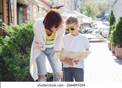 Mom and daughter tourist looking at the map on the street