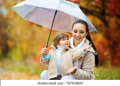 Mom and daughter under the umbrella hide from the rain. Happy funny family with red umbrella under the autumn shower. Girl and her mother are enjoying rainfall. Walk in the park.