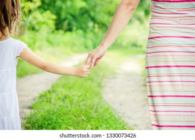 Mom and daughter are walking along the road holding hands. nature.