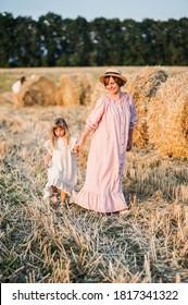 Maman et sa fille marchent dans un champ au coucher du soleil près des magasins de foin
