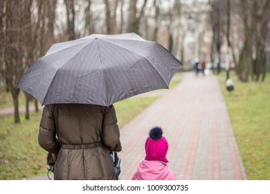 Mom and daughter   walking together with stroller