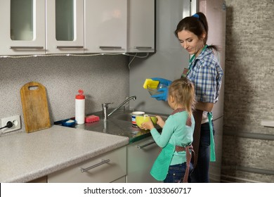 mom and daughter are washing dishes in the kitchen, a woman and a girl doing household chores