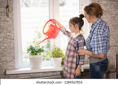 Mom and daughter watering flowers in the apartment, a woman and a girl of three years doing homework