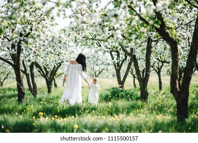 Mom and daughter in white dresses in a blooming garden