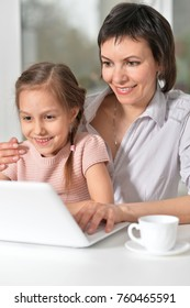 Mom and daughter work at the computer