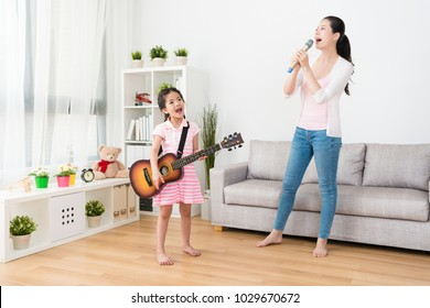 Mom and daughter work together practicing their show in the living room.
