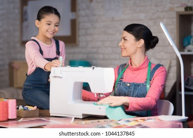 Mom and daughter are working together on the creation of clothes. They are in the sewing workshop in the evening.