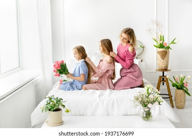 Mom and daughters comb and braid each other's hair. Daily morning care. A bouquet of tulips in the hands of a girl. Care for long hair. Smooth and silky hair after shampooing.