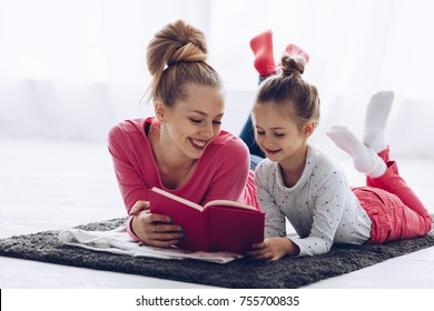 Mom and dauther reading book together. Relationships between parents and children, Education, Comfortable domestic life