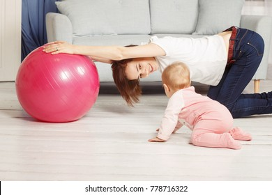 Mom doing exercises on a fit ball with baby. Young woman wearing white t-shirt and blue jeans holding fit ball. Toddler having fun nearby