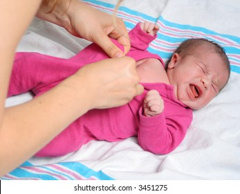 mom dresses up a newborn baby girl in a sleeper