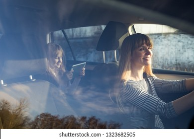 Mom driving car while her daughter sitting on back seat and using digital tablet