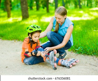 Mom examines the wound of his daughter, who fell skating on roller skates