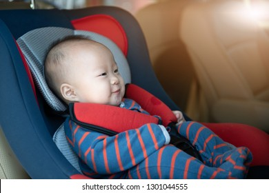 Mom fasten his little baby in the car seat. Asian people in car.